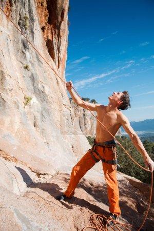 Photo pour Beau grimpeur adulte tenant une corde d'assurage au-dessus du ciel bleu et des montagnes. Turquie, Geyikbayiri - Image de la réserve - image libre de droit