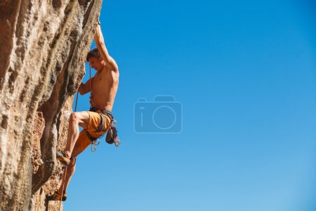 Photo for Rebelious rock climber on the wall against the blue sky - bold choice of real men. Dangerous adventure. Turkey, Geyikbayiri - Stock Image, Close-Up - Royalty Free Image
