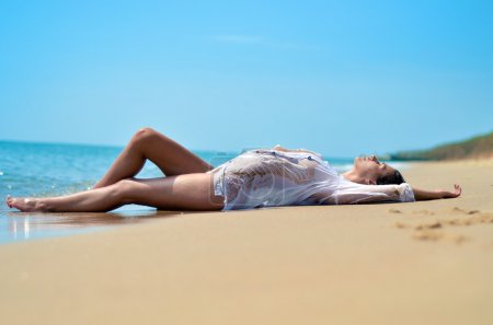 Perfect body girl lies on sand by the sea in white shirt on the wild beach