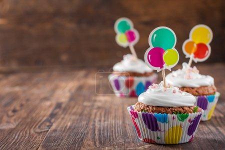 Photo pour Cupcakes au chocolat avec crème sur fond bois foncé - image libre de droit