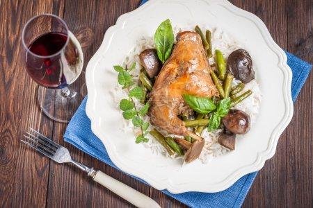 Photo pour Braisé de patte de lapin aux champignons, haricots verts et riz basmati sur une plaque blanche. - image libre de droit