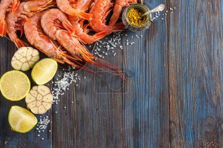 Photo pour Crevettes crues, ail, citron vert, curry et sel de mer sur fond de bois foncé - image libre de droit