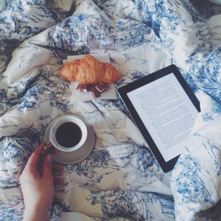 Cup of coffee in hand, eBook and croissant on bed