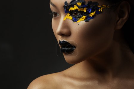 Photo for Portrait of the beautiful asian girl with creative art makeup with bright colors. Picture taken in the studio on a black background. - Royalty Free Image