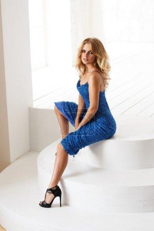 Photo pour Belle femme sensuelle dans la robe étincelante de soirée bleue avec des paillettes est assis dans la salle de lumière en face de la grande fenêtre - image libre de droit