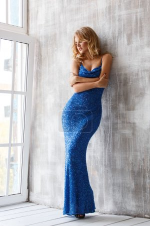 Beautiful smart dressed woman in the blue evening sparkling dress with sequins is posing near the big window