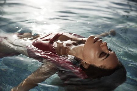 Beautiful sun-tanned woman with closed eyes in the water enjoys her vacation by taking sunbathes in the swimming poll