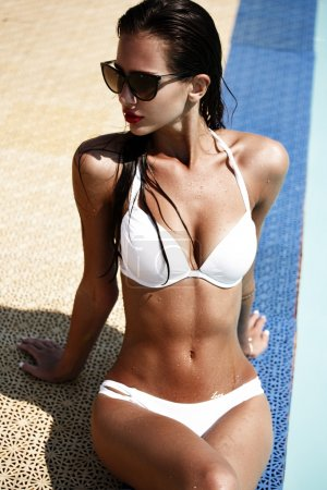 Sexy woman in the white swimsuit on the sun-tanned slim and shapely body is resting and taking sun bathes near the swimming pool