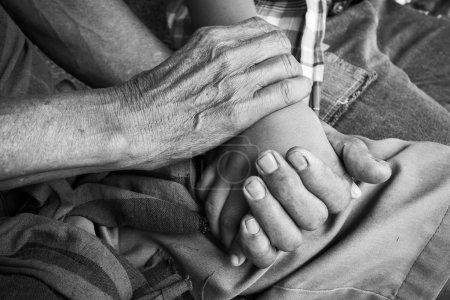 Photo pour Asiatique enfants petit garçon main touches et tient un vieil homme rides mains, noir et blanc ton - image libre de droit
