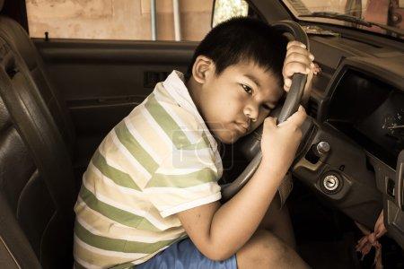 Photo pour Le garçon triste seul dans la voiture ancienne, ton vintage - image libre de droit