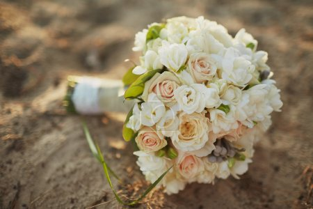 Wedding bouquet with roses lie on the sand