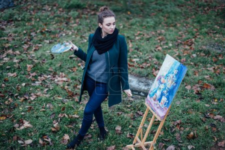 Young woman drawing in easel on the park background
