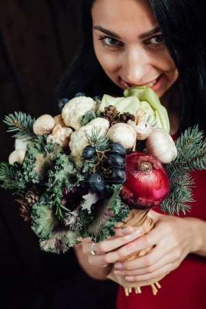 Photo for The original unusual edible bouquet of vegetables and fruits in the girl hands on dark wooden background - Royalty Free Image