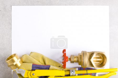 Wrench, working gloves and brass fittings on sheet of paper.