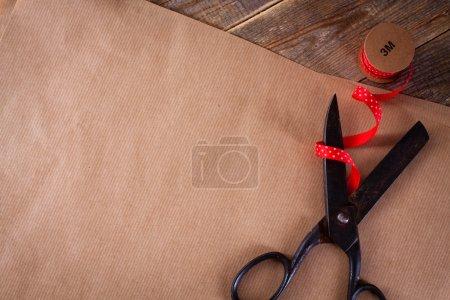 Photo pour Vieux ciseaux, ruban rouge avec gouttes blanches et papier d'emballage sur fond en bois . - image libre de droit