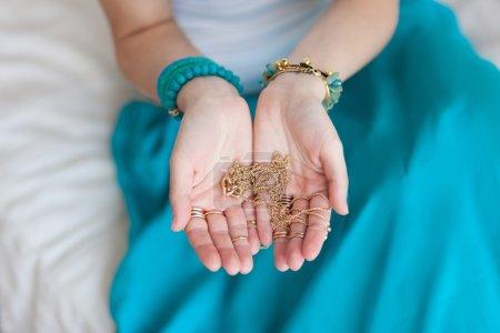 Photo pour Chaîne d'or dans les mains d'une jeune femme orientale attrayante. Fond flou. Jupe bleue, bijoux en or, Maroc, une journée ensoleillée . - image libre de droit