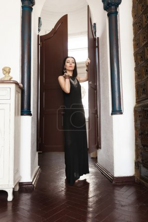 Luxurious dark-haired woman in a black dress and a massive gold jewelry