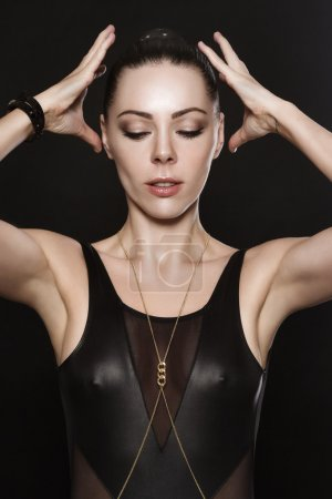 Beautiful young woman in leather garment raises her hands to her head.
