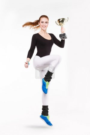 Young red-haired athletic girl with championship trophy