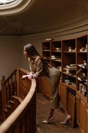 Photo pour Belle jeune femme élégante sur le balcon dans la bibliothèque vintage . - image libre de droit