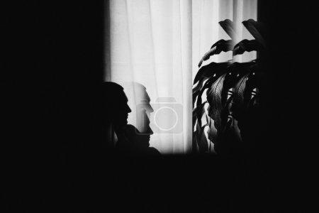 Photo pour Homme mystérieux assis avec des ombres près de la fenêtre. Fond sombre . - image libre de droit