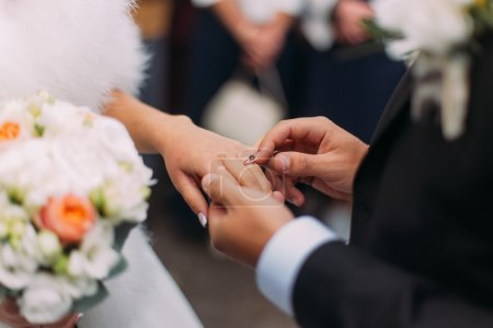 Close-up of elegance groom putting wedding ring on fingers lovely bride