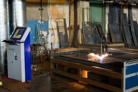Bright orange sparks during metal grinding in heavy industry plant