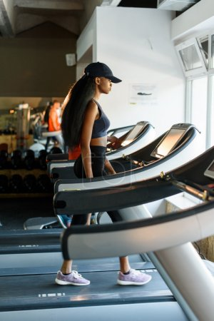 Running on treadmill in gym or fitness club - sexy black woman exercising to gain more fit
