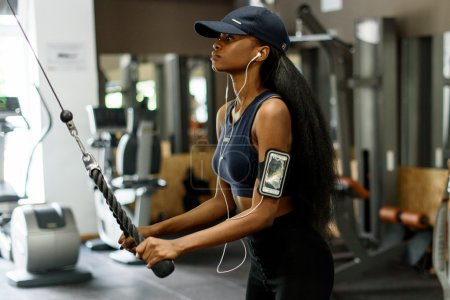 Side view of sexy gorgeous african-american woman working out at the gym and listens to music in white earphones