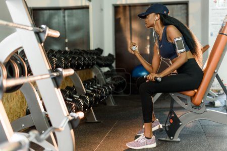 Side view of sporty fitness african american woman working out with dumbbells at the gym and listens music in earphones