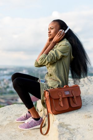 Fashion portrait of beautiful african american hipster young woman with smartphone and headphones listening to music over blue cloudy sky background