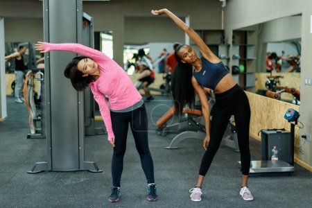 Slim black african-american fitness instructor and asian lovely woman doing exercise work together in the gym