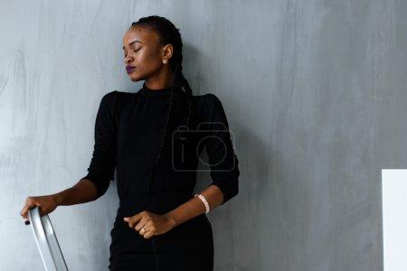 Pretty african or black american woman standing closing eyes on dark gray studio background