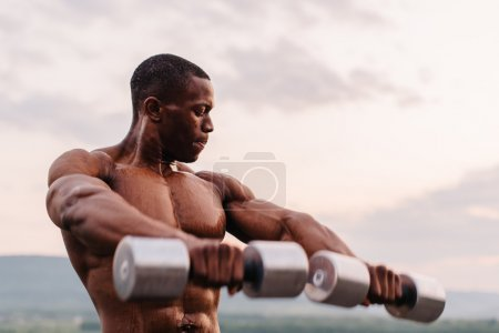Handsome african american muscular man lifting dumbbells against the sunset sky background