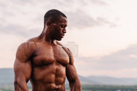 Portrait of handsome black african american athlete on the sunrise sky background