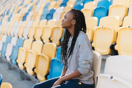 Photo pour Femme américain africain excité dans le sportswear gris regardant loin s'asseyant sur des gradins attendant un spectacle, célébration. - image libre de droit