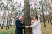 Just mariied outdoor portrait. Cute white dressed bride with her handsome groom posing in green pine forest near high conifer tree