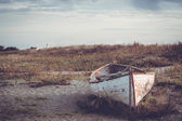 Old, weathered, beached boat.