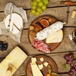 Red wine, various types of cheese, salami and grap...