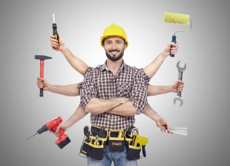 Photo for Cheerful carpenter looking at camera with tolls in six hands - Royalty Free Image