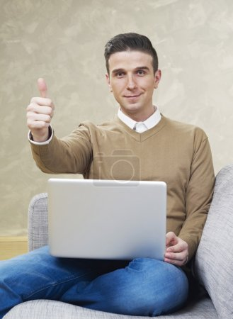 Man on couch with laptop showing ok sign
