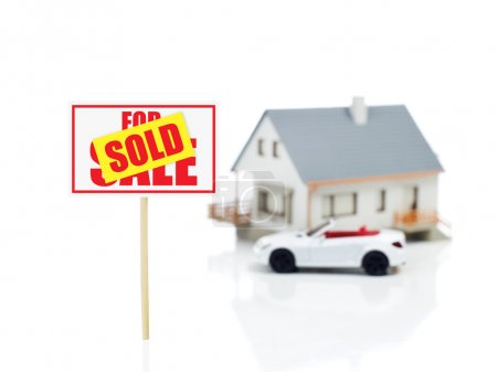 sold sign and house model and car