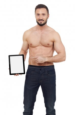 Muscular man pointing to a digital tablet