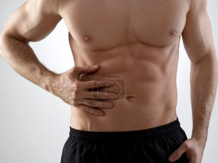 Photo for Sportsman with abdomen pain, isolated on gray - Royalty Free Image