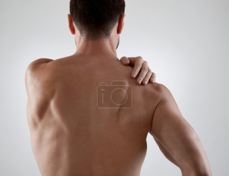 Photo for Sportsman with shoulder pain, gray background - Royalty Free Image