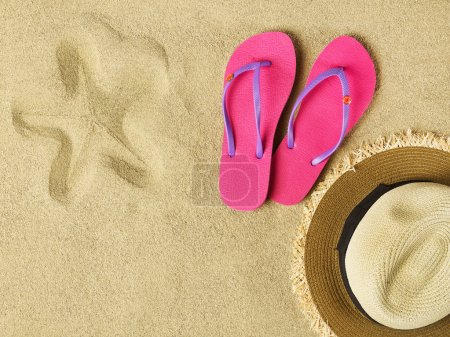 Slippers and hat on sand
