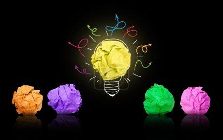 Photo pour Boule de papier formant une ampoule électrique avec les autres boules de papier multicolores autour, fond noir - image libre de droit