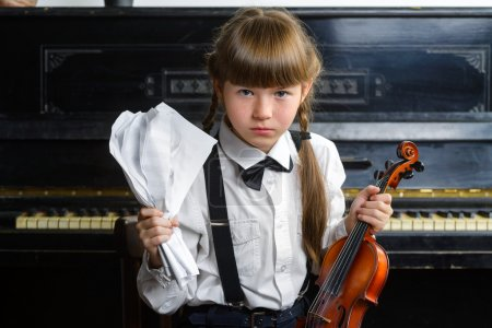 distraught or distressed girl clutching her head and holding a violin
