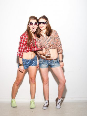 Close up fashion lifestyle portrait of two young hipster girls best friends, wearing bright make up and trendy clothes, making funny faces and have gray time. Urban  background.
