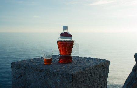 Photo pour Une table de restaurant sur une plage au coucher du soleil avec deux verres de vin blanc et un seau à glace - image libre de droit
